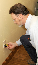 Home inspector with Rushmore Inspection Services testing outlets